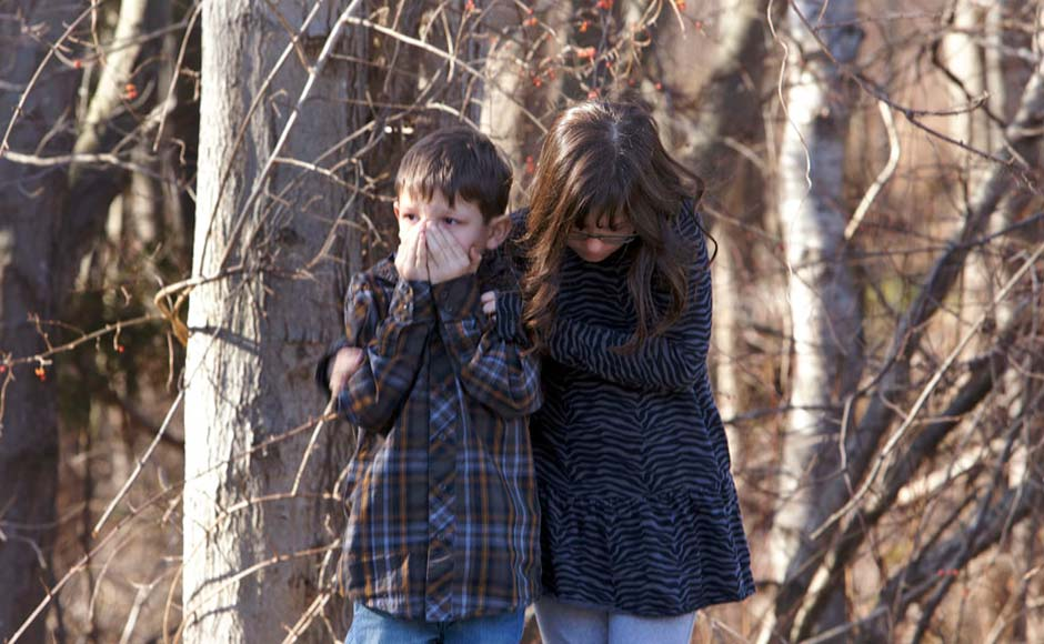 First-grader Henry Terifay and his sister, fourth-grader Kelly Terifay, wait outside Sandy Hook Elementary School after a shooting in Newtown, Connecticut. Michelle Mcloughlin/ Reuters