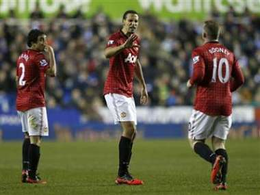 Manchester United's Rio Ferdinand congratulates team mate Wayne Rooney after Rooney scored during their English Premier League soccer match against Reading at the Madejski Stadium in Reading. Reuters
