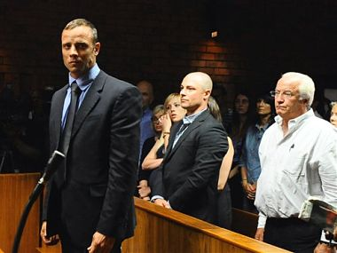 Olympian Oscar Pistorius, foreground, stands following his bail hearing, as his brother Carl, centre, and father Henke, right, look on,  in Pretoria, South Africa. AP