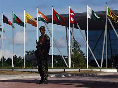 A Maldives army soldier stands guard near the flags of the South Asian Association for Regional Cooperation (SAARC). Reuters
