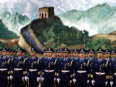 An honour guard stand in front of a painting depicting the Great Wall before the start of an official welcoming ceremony for South Korea's Prime Minister Kim in the Great Hall of the People in Beijing