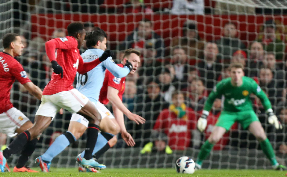 Manchester United players fail to stop Manchester City's Sergio Aguero, from breaking through to score during their English Premier League soccer match. AP