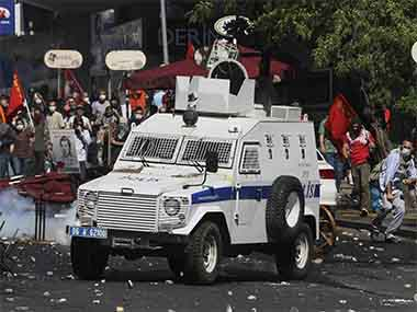 A Turkish protester, right,  throws a stone at police vehicle as the protesters clash with security forces in Ankara, Turkey, Saturday, June 1. AP