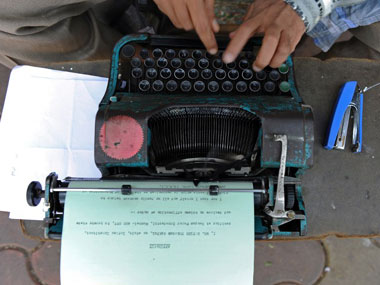 A man works on a typewriter in India. AFP.