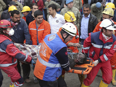 Rescue workers carry the dead body of a miner from the mine in Soma, western Turkey. AP