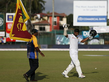 Sri Lanka's Kumar Sangakkara (R) waves his bat at fans as he walks off the field for one last time in international cricket. Reuters
