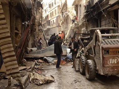 In this file image, Syrians gather between damaged buildings in the predominantly Christian and Armenian neighborhood of Suleimaniyeh, Aleppo, Syria.  AFP