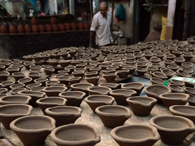 A potter arranges earthen lamps at a workshop in Dharavi. AFP