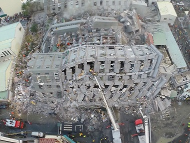 Rescue workers search a collapsed building from an early morning earthquake in Tainan, Taiwan. AP
