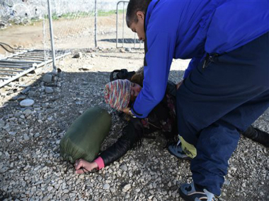 An afghani woman collapses at a checkpoint of the borderline with Macedonia. AP