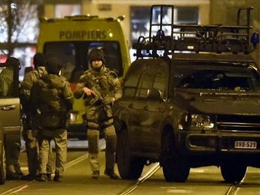 Special operations police take positions during a raid in Brussels. AP