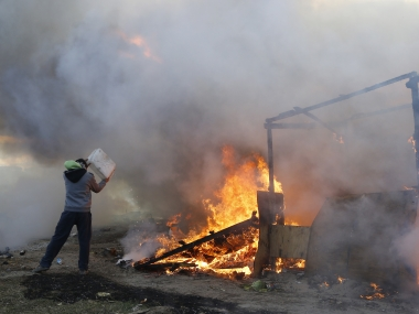 A man throws water on burning tents in a makeshift camp near Calais, France. AP