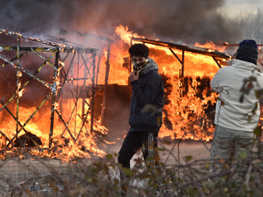 "A migrant walks past shacks burning during the dismantling of half of the ""Jungle"" migrant camp in the French northern port city of Calais, on February 29, 2016. Clashes broke out between French riot police and migrants on February 29 as bulldozers moved into the grim shantytown on the edge of Calais known as the ""Jungle"" to start destroying hundreds of makeshift shelters. AFP"