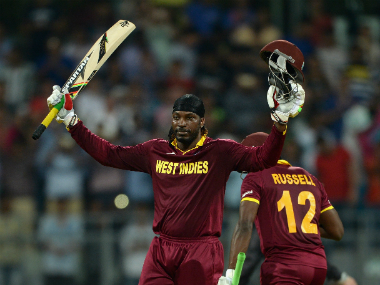 Chris Gayle raises his bat after completing his century in just 47 deliveries. Getty Images