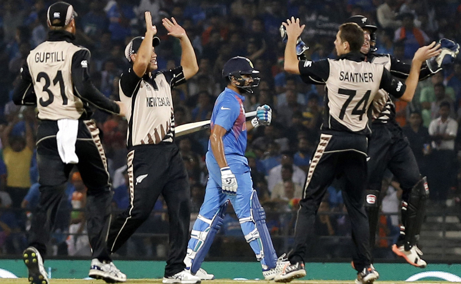 Mitchell Santner (2nd from right) celebrates the dismissal of Rohit Sharma (centre) with the rest of the New Zealand team. PTI