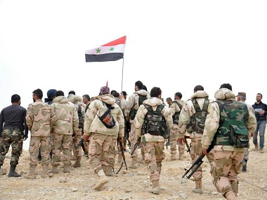 Syrian soldiers gather around a Syrian national flag in Palmyra. SANA via AP