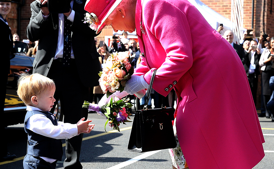 Queen Elizabeth II is presented with flowers as she leaves the Queen Elizabeth II delivery office in Windsor on 20 April in Windsor, Britain. The visit marks the 500th Anniversary of the Royal Mail delivery service. The Queen and Duke of Edinburgh are carrying out engagements in Windsor ahead of the Queen's 90th Birthday on 21 April. Reuters