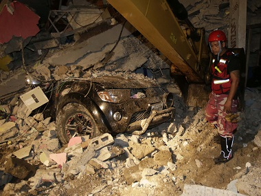 A rescue worker searches in the rubble of a destroyed house in Pedernales, Ecuador on Sunday. AP