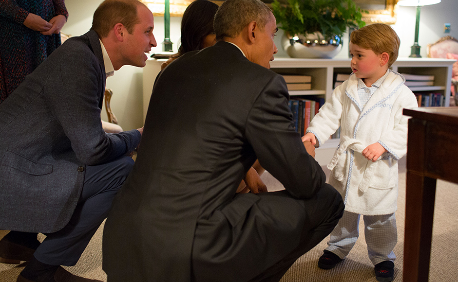 US President Barack Obama, Prince William, Duke of Cambridge and First Lady Michelle Obama talks with Prince George at Kensington Palace in London, England. Getty Images