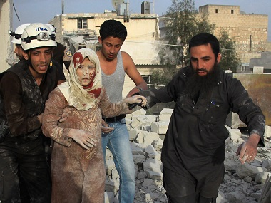 Syrian rescue workers and residents help an injured woman following a reported air strike by government forces on the rebel-held neighbourhood of Haydariya in Aleppo on Sunday. AFP