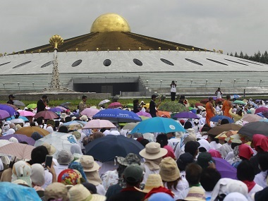 Buddhist devotees sit outside the Wat Phra Dhammakaya temple as police serve an arrest warrant for its abbot. AP
