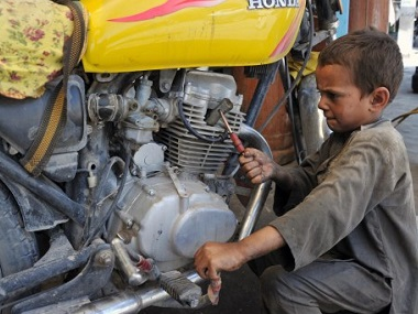 An Afghan child labourer works at a motorcycle mechanic shop in Jalalabad. AFP
