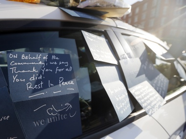 A note left by an unknown person on the door window of a Dallas police cruiser thanks law enforcement officers for their service, Friday, July 8, 2016, in Dallas. The cruiser sits along side a Dallas Area Rapid Transit cruiser in front of Dallas Police Department headquarters and is serving as a makeshift memorial. (AP Photo/Tony Gutierrez)