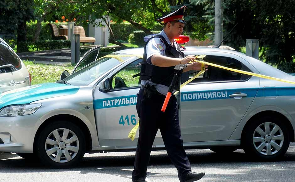 A police officer wraps up police tape at a street in Almaty, Kazakhstan. Two gunmen attacked a police station in central Almaty late Monday morning, killing three police officers in a gun battle. Reuters