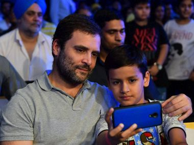 Rahul Gandhi with a child at the WBO Asia Pacific Middleweight Championship at Thyagaraj Sports Complex in New Delhi. PTI