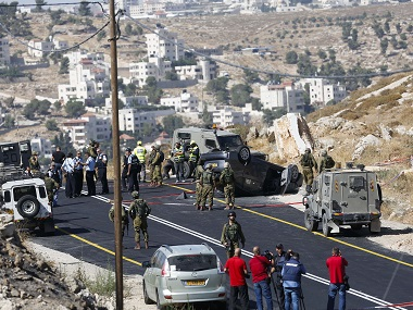 Israeli soldiers secure the scene of a car crash after a shooting attack near Hebron, West Bank, on 1 July. AP
