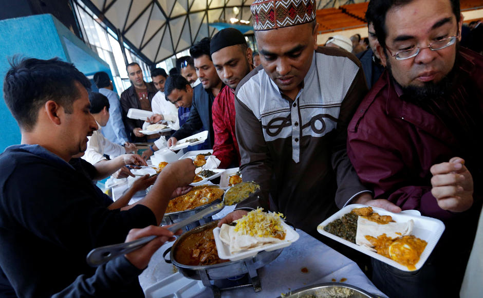 Muslim men of Mexico's Islamic community receive a meal during Eid al-Fitr celebrations, which marks the end of the Muslim fasting month of Ramadan, in Mexico City, Mexico. Reuters