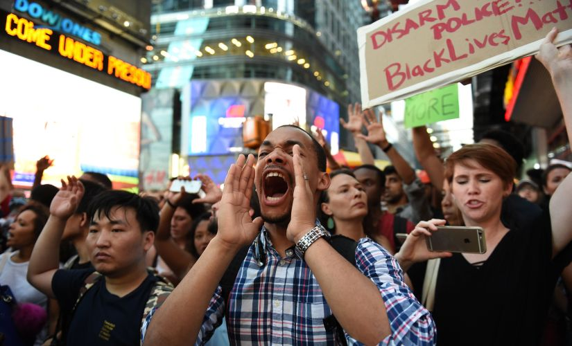 Protesters shout slogans in New York City against the shooting of two black men on Thursday. AFP