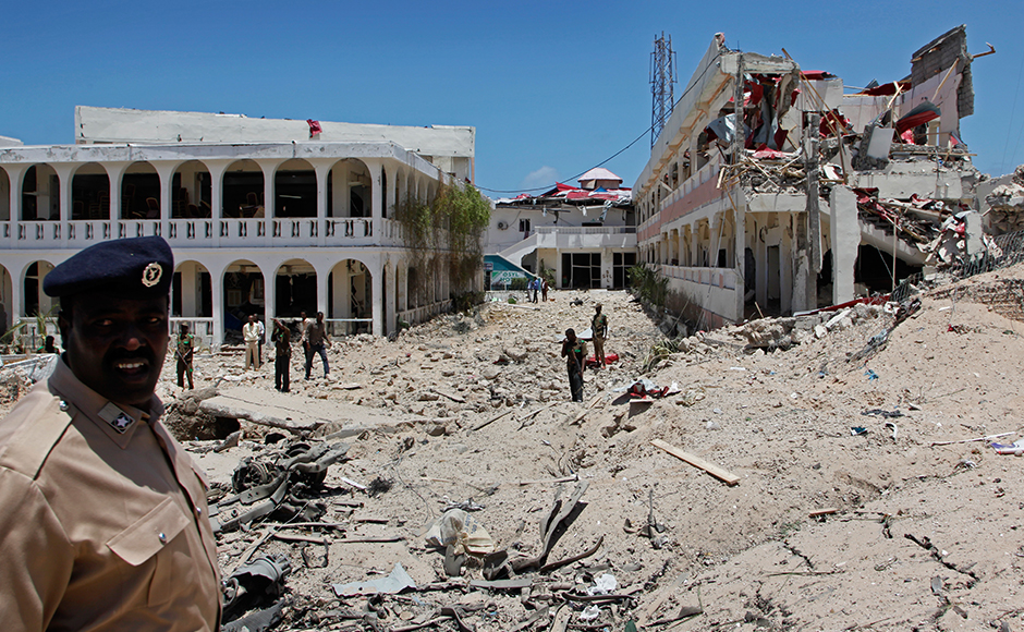 Somali soldiers stand near to a building destroyed by a blast near the presidential palace in the capital Mogadishu, Somalia Tuesday, Aug. 30, 2016. A suicide bomber has detonated an explosives-laden truck near the gate of Somalia's presidential palace in the capital on Tuesday, killing at least 12 people, police say. AP