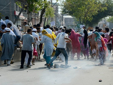 Srinagar: Protesters runs for cover amid tear gas smoke fired by police to disperse them during clashes in Srinagar on Wednesday. PTI
