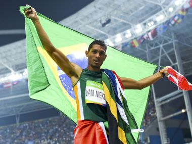 First placed Wayde van Niekerk of South Africa celebrates with Brazilian flag. Reuters