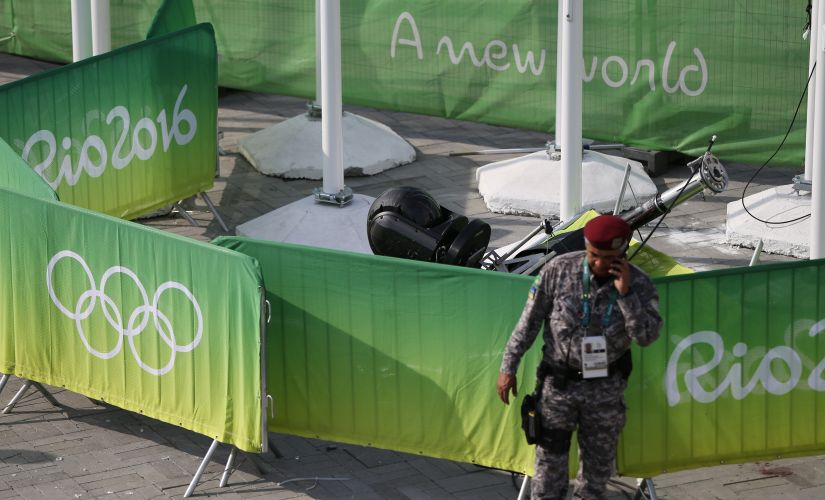 A policeman stands near an overhead television camera that fell and injured people near the Olympic Park. Reuters