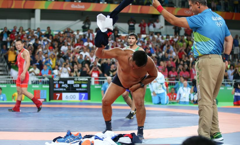 2016 Rio Olympics - Wrestling - Final - Men's Freestyle 65 kg Bronze - Carioca Arena 2 - Rio de Janeiro, Brazil - 21/08/2016. The coach of Mandakhnaran Ganzorig (MGL) of Mongolia takes off his clothes as he protests after the match against Ikhtiyor Navruzov (UZB) of Uzbekistan. REUTERS/Toru Hanai TPX IMAGES OF THE DAY. FOR EDITORIAL USE ONLY. NOT FOR SALE FOR MARKETING OR ADVERTISING CAMPAIGNS. - RTX2MFJ3