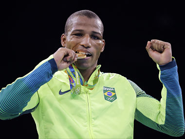 Brazil's Robson Conceicao bites his gold medal for the men's lightweight 60-kg final boxing. AP