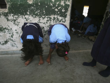 Schoolgirls serve a punishment meted out to them by their teacher outside a classroom at a government-run primary school in Noida. Reuters