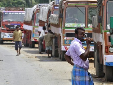 A truck driver brushes his teeth next to his parked truck while waiting to get his loads cleared to cross a checkpoint at the Commercial Taxes Department check post at Walayar in Palakkad district in southern Indian state of Kerala, India, September 5, 2015.  At the Walayar checkpoint in southern India, lines of idle trucks stretch as far as the eye can see in both directions along the tree-lined interstate highway, waiting for clearance from tax inspectors that can take days to complete. The rollout of a nationwide goods and services tax (GST) from April was supposed to sweep away hundreds of checkposts on India's state borders, paving the way for the seamless movement of goods from the tropical south to the Himalayas in the north. But political opposition and the dilution of some of the tax's key tenets mean hopes are fading that the checkposts will be demolished any time soon, a major blow for Prime Minister Narendra Modi's reform agenda - and for India's economy. Picture taken September 5, 2015.  REUTERS/Sivaram V - RTS1MYZ