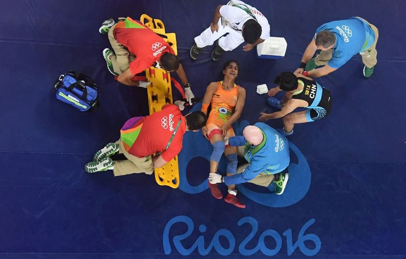 Injured Vinesh Phogat of India is treated by medical staff. Getty Images