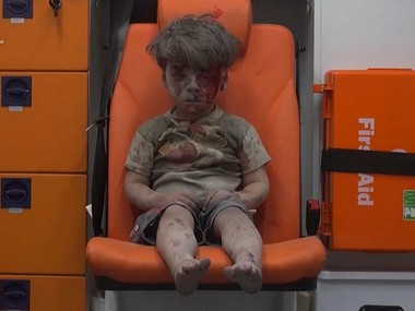 In this frame grab taken from video provided by the Syrian anti-government activist group Aleppo Media Center (AMC), a child sits in an ambulance after being pulled out or a building hit by an airstirke, in Aleppo, Syria, Wednesday, Aug. 17, 2016. Syrian opposition activists reported an airstrikes on the al-Qaterji neighborhood in Aleppo late Wednesday. (Aleppo Media Center via AP)