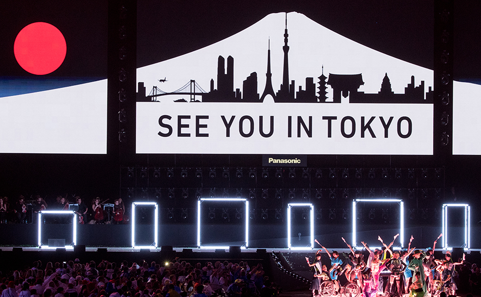 """Koichi Omae and four female dancers are joined on stage by GIMICO, Aya Sato, Bambi and Akira Hiyama as a sign saying """"see you in Tokyo"""" appears behind the performers during the closing ceremony. (Simon Bruty/OIS, IOC via AP)"""