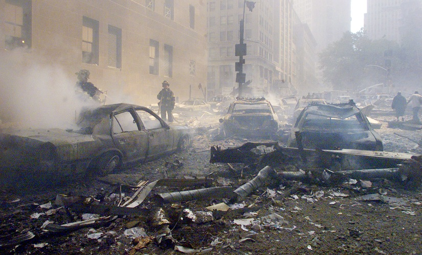 FILE PHOTO - Cars smoulder in the street as the destroyed World Trade Center burns in New York on September 11, 2001. Two hijacked commercial planes slammed into the twin towers of the World Trade Center causing both 110-story landmarks to collapse in thunderous clouds of fire and smoke. REUTERS/Peter Morgan JC/SV - RTR910Z