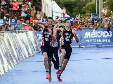 Alistair Brownlee helps his brother Jonathan Brownlee before crossing the line in second and third place during the ITU World Triathlon. AFP