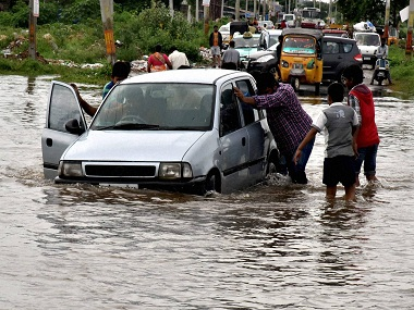 Hyderabad: People pushing a car through a flooded road at Bellapure after heavy downpour in Hyderabad on Friday. PTI Photo (PTI9_23_2016_000269B) *** Local Caption ***