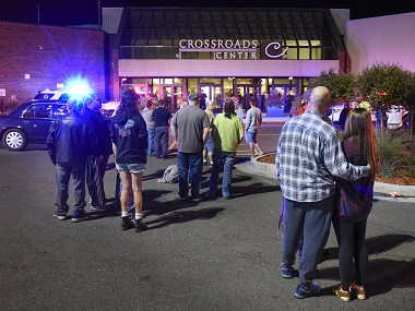 People stand near the entrance on the north side of Crossroads Center shopping mall in St. Cloud, Minn., Saturday, Sept. 17, 2016. Several people were taken to a hospital with injuries after a stabbing attack at the mall, which ended with the suspected attacker dead inside the mall. (Dave Schwarz/St. Cloud Times via AP)