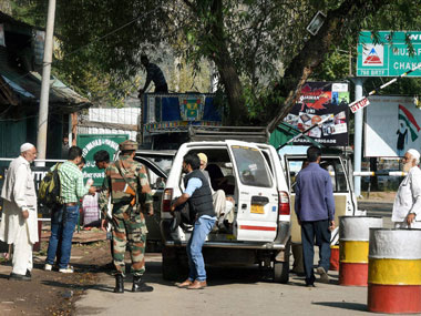 An Army person inspects a passenger vehicle at the checkpost near Uri Army Brigade on Thursday. The road, passing through the brigade headquarters connecting 12 villages close to the LoC, was opened to civilian traffic after remaining closed for four days in view of the recent attack on the army base. PTI