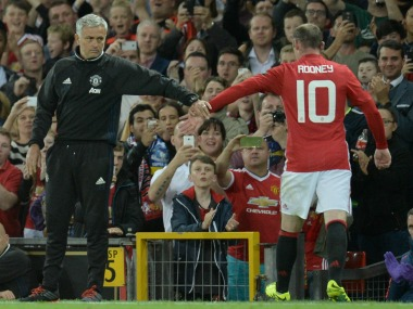 Wayne Rooney (R) touches hands with Jose Mourinho as he leaves the pitch after being substituted. AFP
