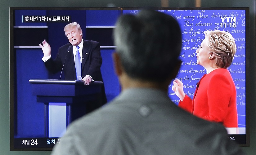 A man watches a TV screen showing the live broadcast of the US presidential debate between Democratic presidential nominee Hillary Clinton and Republican presidential nominee Donald Trump, at Seoul Railway Station in Seoul, South Korea. AP